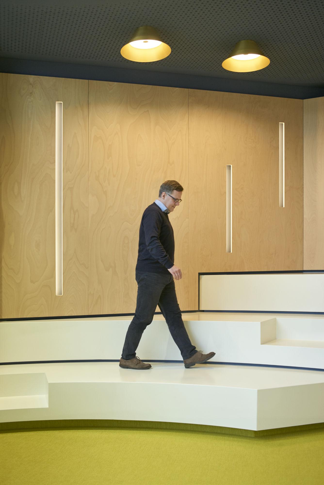 Geschäftsführer läuft auf Bank in Auditorium und blickt nach vorne unten