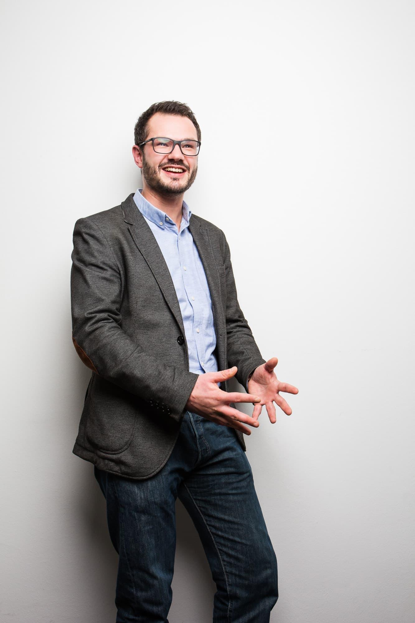 Prof. Robert Böhm gestikuliert vor weißer Wand