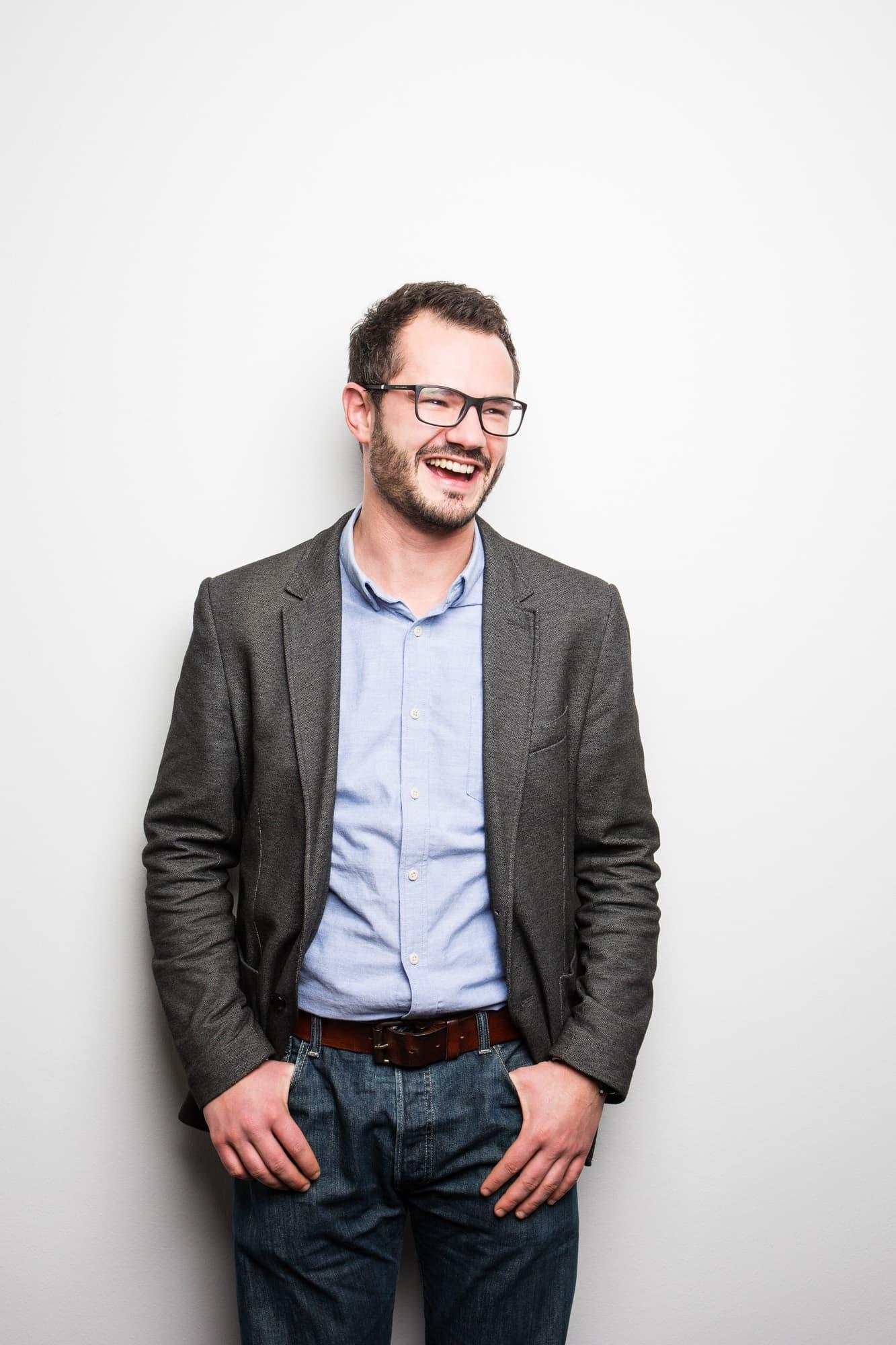 Prof. Robert Böhm lacht mit Händen in der Hosentasche vor weißer Wand
