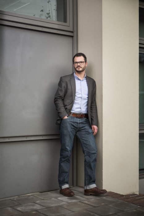 Prof. Robert Böhm lehnt gelassen an einer Wand und blickt in die Kamera