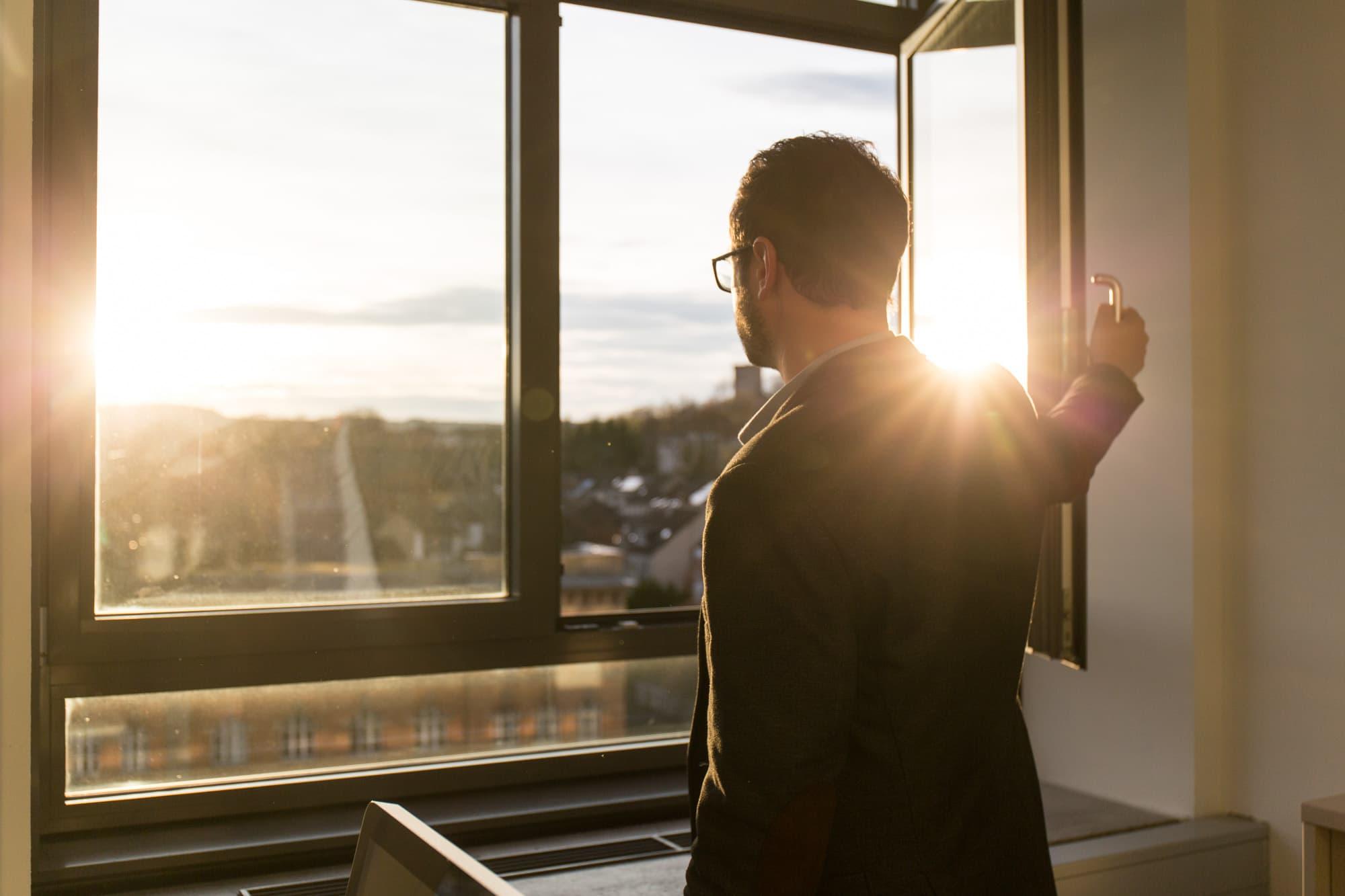 Prof. Robert Böhm blickt aus dem Fenster auf das die Abendsonne scheint