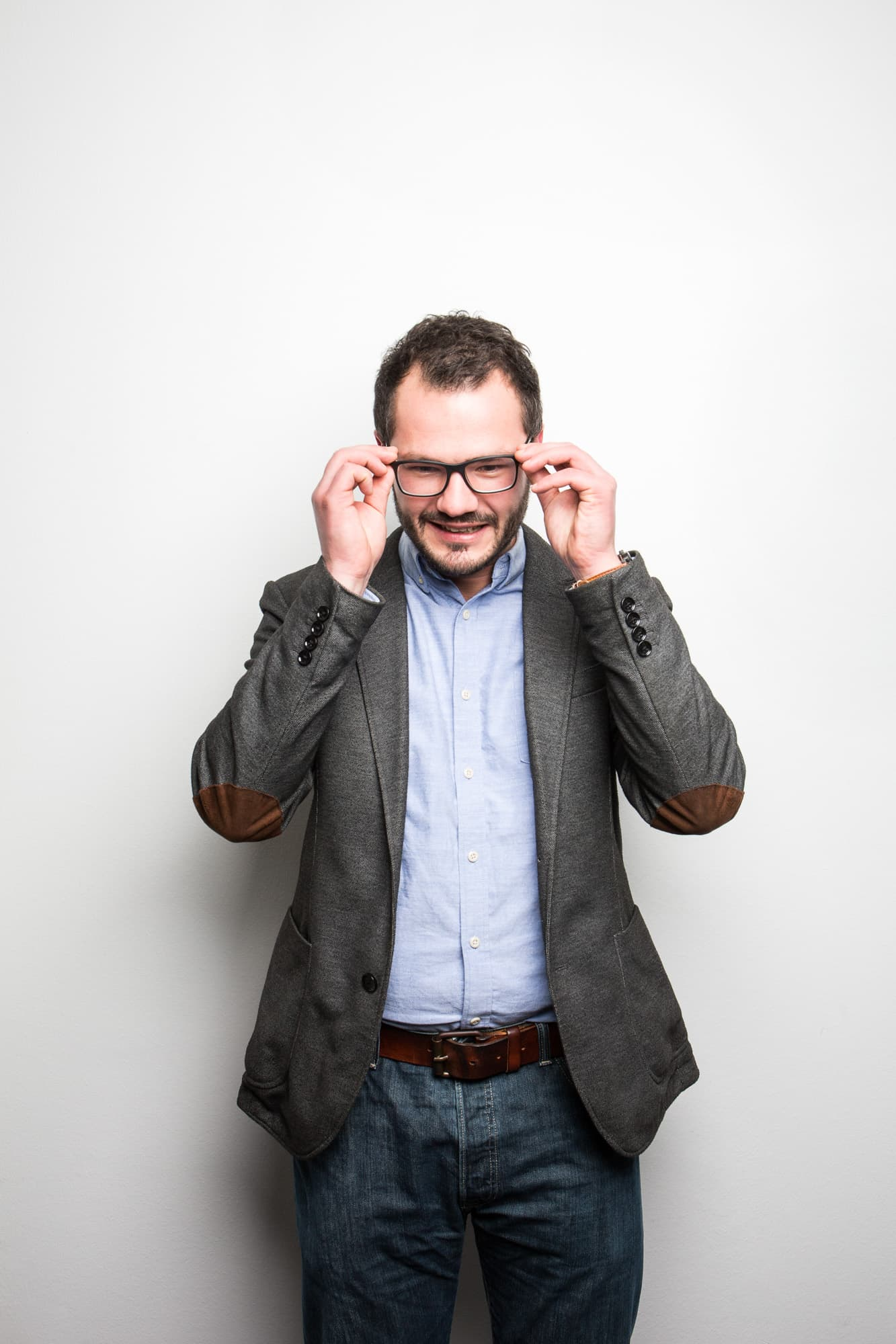 Prof. Robert Böhm richtet sich die Brille vor weißer Wand