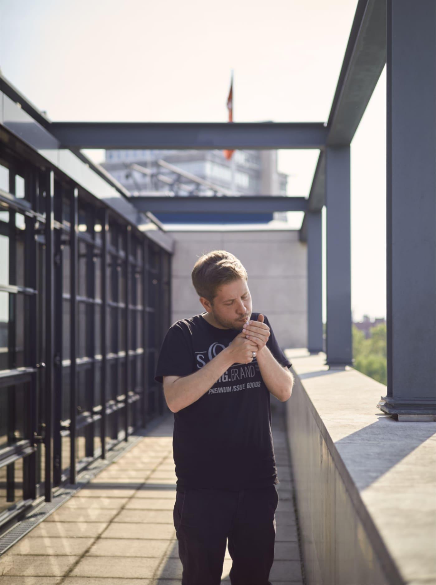Kevin Kühnert zündet sich eine Zigarette an im Willy Brandt Haus