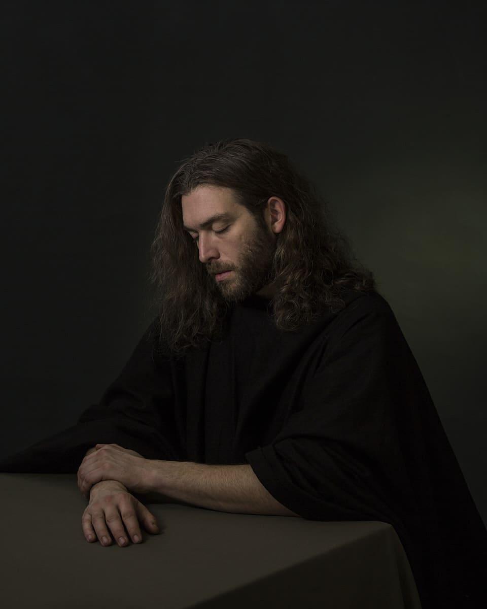 Bild eines Mannes mit verschränkten Armen an einem Tisch sitzend, vor einfarbigem Hintergrund